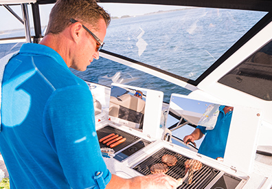 Man grilling on the MarineMax Vacations 362 Power Catamaran