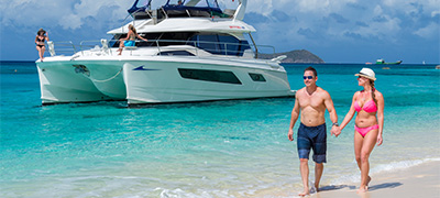 Couple walking on beach with MarineMax Vacations 443 Power Catamaran in background