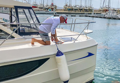Man installing bumbers to side of boat docked in water
