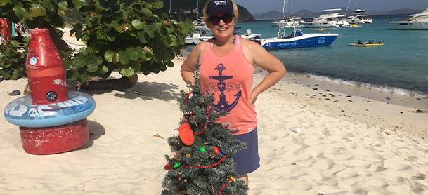 A woman on a beach in front of a Christmas tree