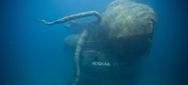 A sunken ship named Kodiak Queen with a large octopus sculpture placed on it