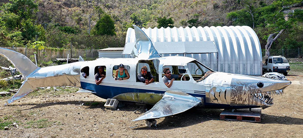 A deconstructed airplane made to look like a shark, resting on a beach in the British Virgin Islands