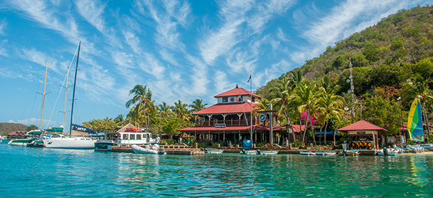 The Bitter End Yacht Club in the British Virgin Islands on a sunny day, with boats docked outside