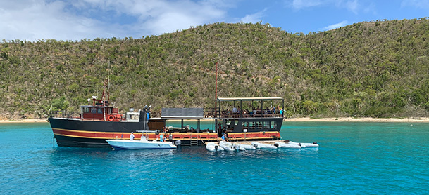 The Willy T floating bar, a black vessel anchored near the coast of the British Virgin Islands