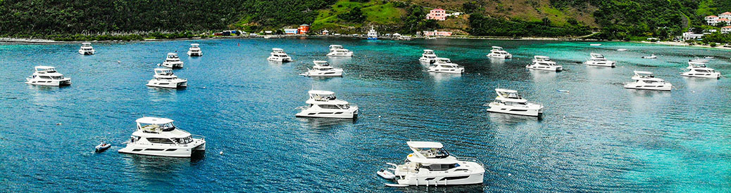 A wide shot of a group of Aquila power catamarans in clear blue-green water off the coast of the British Virgin Islands