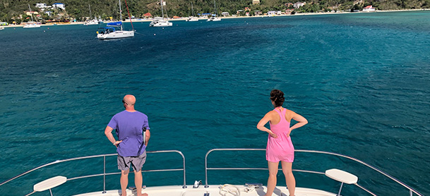 A man and woman standing at the stern of an Aquila power catamaran, looking off at the coastline of the British Virgin Islands