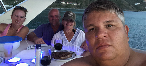A selfie of a man on a boat with another man and two women, seated at the table on an Aquila power catamaran