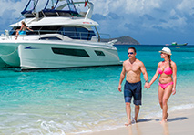 Couple walking on beach in Caribbean with power catamaran yacht anchored in background.