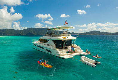 A MarineMax power catamaran idle in clear water with people kayaking, paddleboarding, and snorkeling