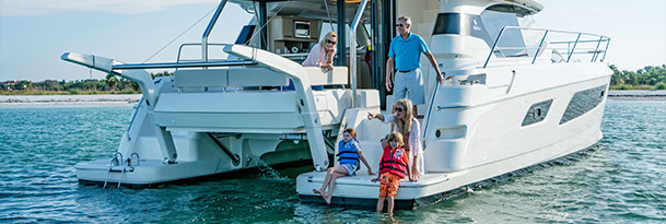 family on aft of aquila 44 power catamaran during charter trip