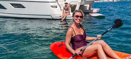 women kayaking in british virgin islands with charter boat in background
