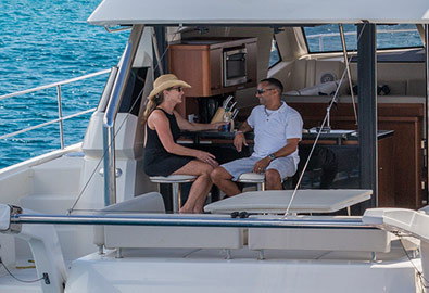 Couple setting at aft bar on charter power catamaran