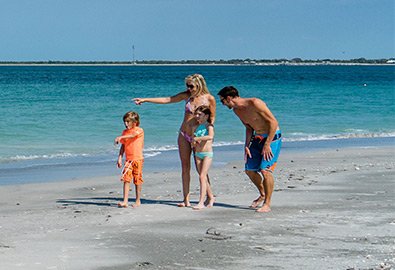 Family walking on beach with blue water