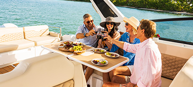 People raising glasses while eating aboard a boat