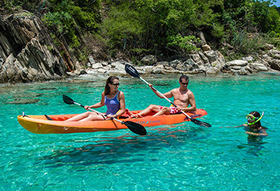 A couple kayaking next to a girl snorkeling