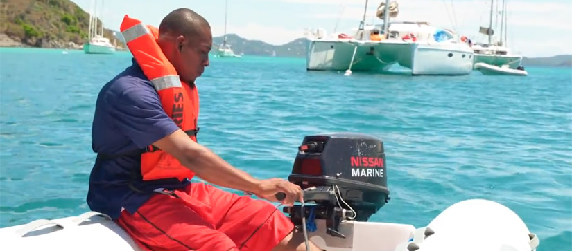 Man in life jacket powering dinghy boat engine