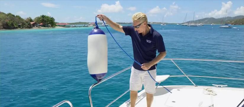 Man tying on a boat fender