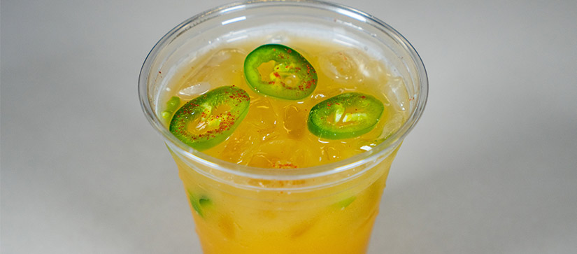 orange drink in a cup with jalapeno slices