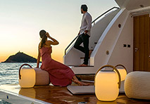 A man and woman looking off of the stern of a yacht