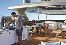 man grilling for family on deck of yacht