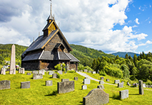 Church and cemetery on green hills in Norway