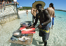 Man preparing fish on edge of water in Abacos Islands