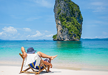 Person sitting on beach by the water in Thailand