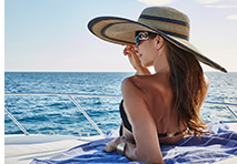 woman with large hat lounging on the bow of a yacht