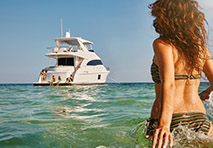 woman in bikini with long hair running through water towards yacht