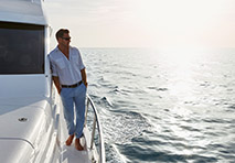 man leaning against the side of a yacht overlooking the open water