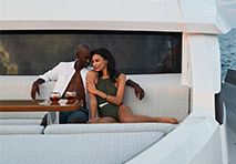 man and woman sitting together on bow of a large yacht