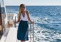 woman standing on deck of a yacht looking out to the water