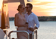 couple on balcony of ocean alexander with sunset behind them