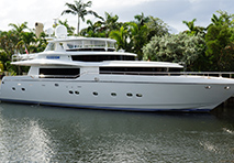 a profile view of the yacht illusion docked in a waterway with palm trees behind it