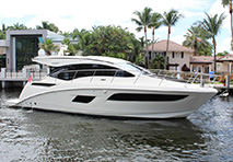 a profile view of a sea ray 400 sundancer in a waterway with houses and palm trees behind it