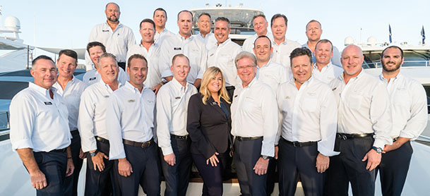 A group of yacht brokerage consultants smiling on a dock.