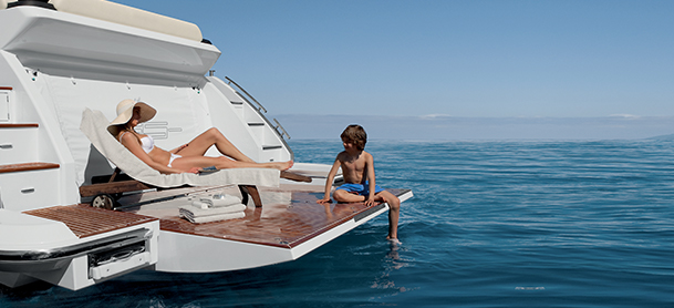 Woman and child relaxing on deck of yacht by the water