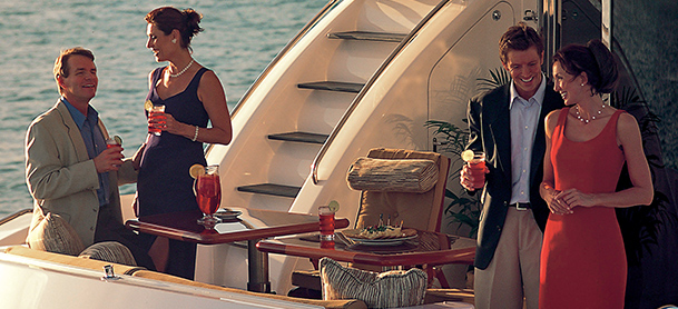 Couples enjoying evening drinks aboard yacht