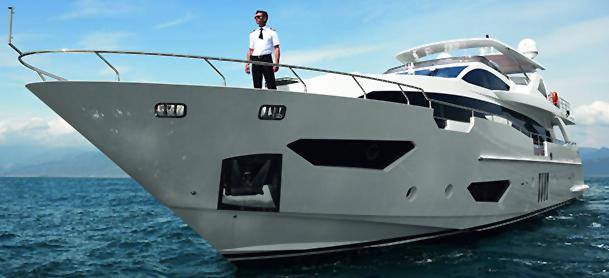 Man standing aboard yacht on water