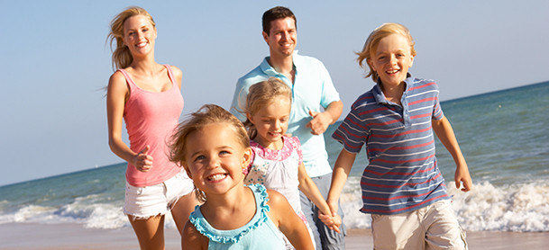 A family walk along a beach while smiling with waves crashing behind them