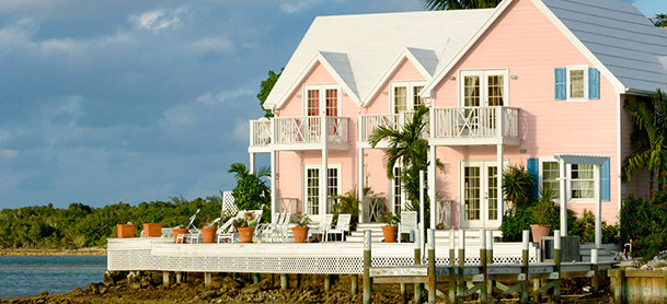A pink waterfront house with a white deck