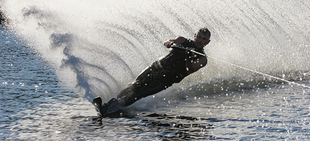 A man waterskis while leaving a big wave behind him