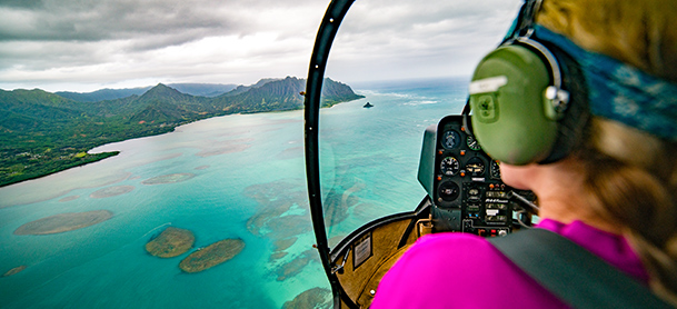 A woman looks out of a helicopter over a coastline