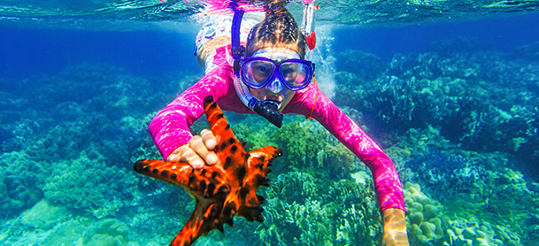 A girl wearing snorkeling equipment holds an orange starfish underwater