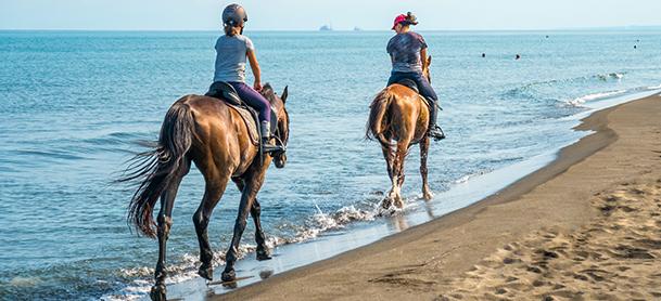 Two women ride horses along a beach