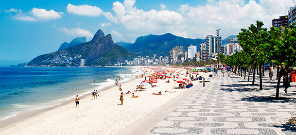 A crowded beach with a city skyline and mountains in the background