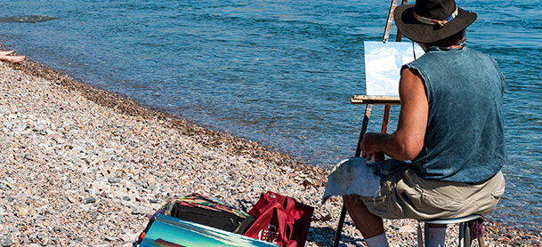 A man sits on a rocky beach and paints the ocean in front of him