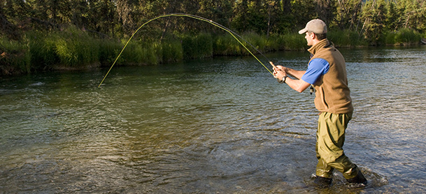 A man stands in ankle-deep water while fishing
