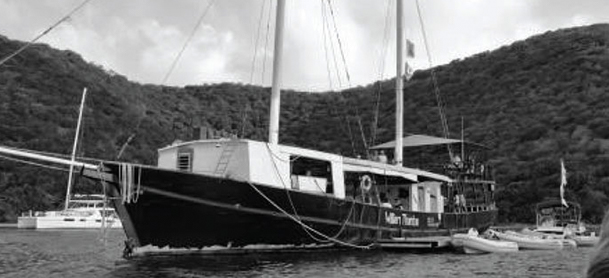 A sailboat rests in the water with hills on the land behind it