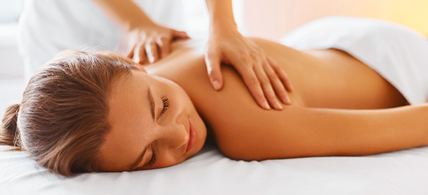 A woman lays down while getting a back massage